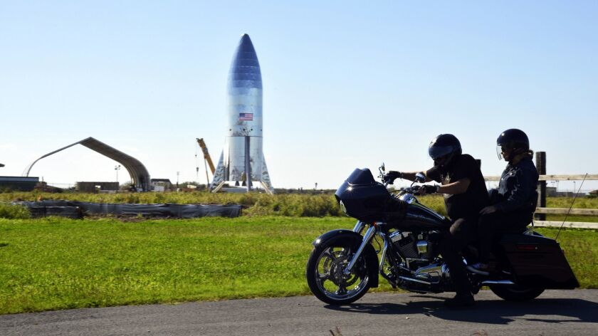FILE - In this Jan. 12, 2019 file photo, a motorcyclist rides near the SpaceX prototype Starship hop