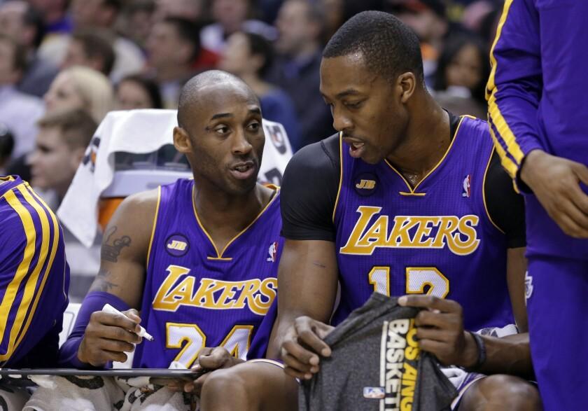 Lakers guard Kobe Bryant, left, draws up a play for center Dwight Howard last season.