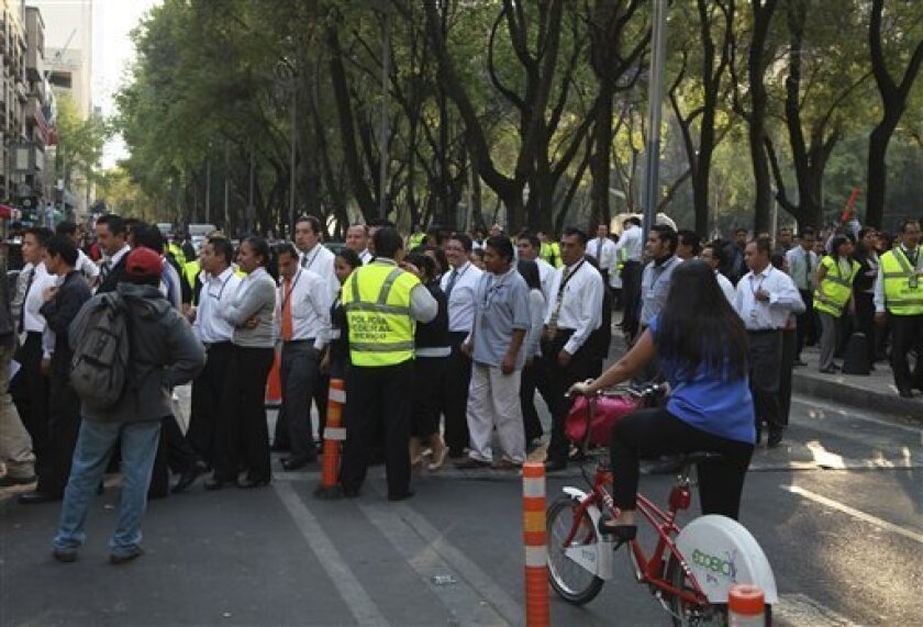 People begin returning to a building that was evacuated after an earthquake was felt in Mexico City, Mexico, Wednesday, April 11, 2012. The U.S. Geological Survey reported a preliminary reading of 7.0 magnitude for the quake, which it said was centered 238 miles (384 kilometers) west-southwest of Mexico City and 88 miles (143 kilometers) northwest of the Pacific resort of Zihuantanejo. (AP Photo/Dario Lopez-Mills)