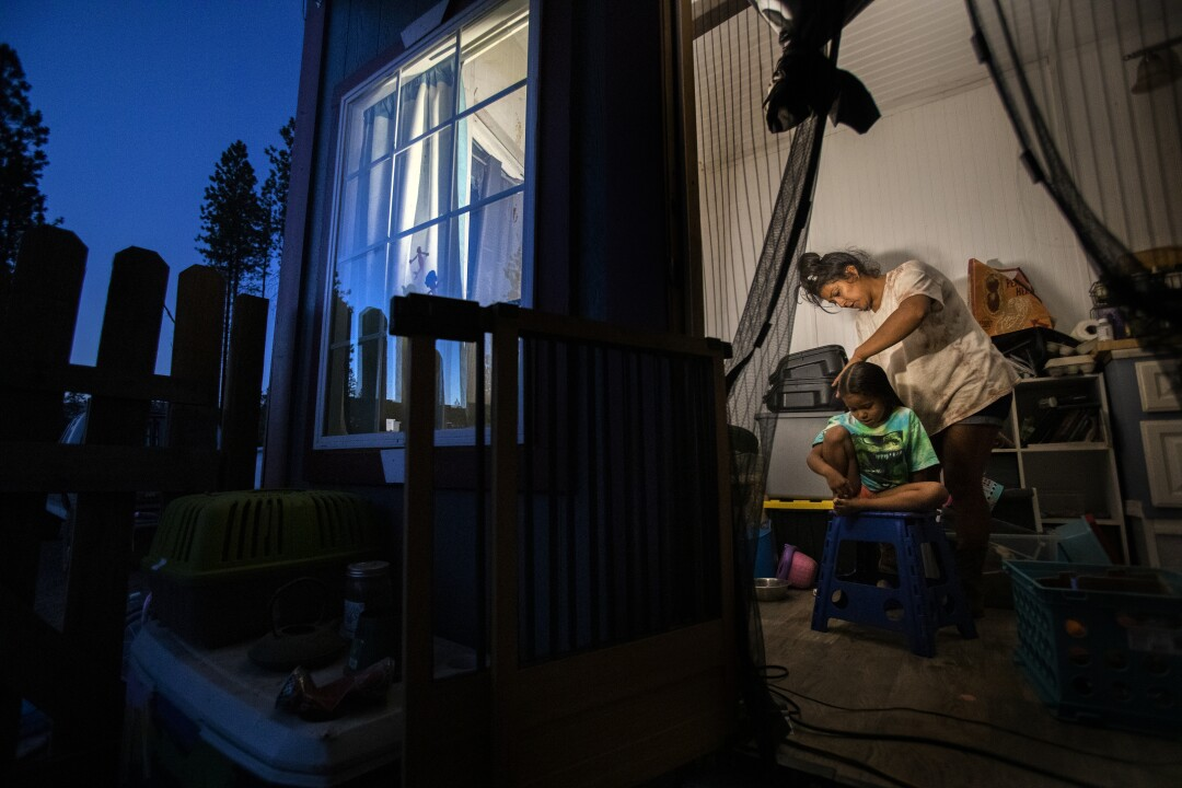 Inez Salinas brushes her daughter's hair inside their tiny home.