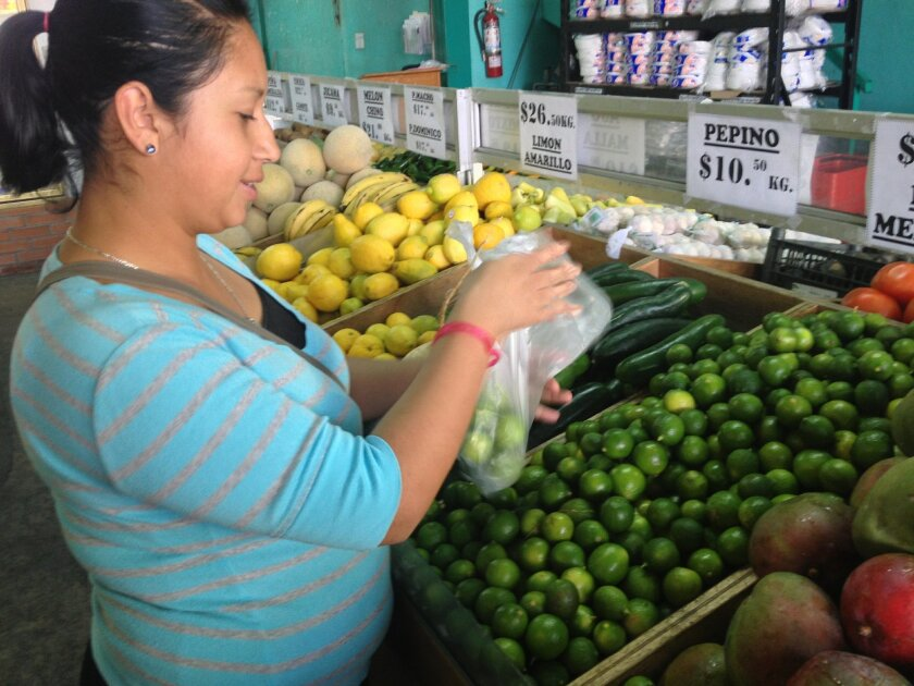 Lizbeth Ventura, 25, shops for limes Tuesday at Tijuana's Mercado de Abastos.