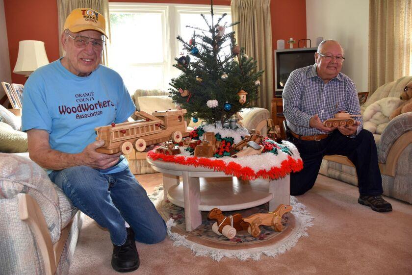Los miembros de la organización no lucrativa Orange County Woodworkers de California, Bill Rogers (i), de 82 años, y José 'Pepe' Ulloa, 73, posan con unos juguetes de madera en City of Orange, California. Son, en su mayoría, ancianos y veteranos de las Fuerzas Armadas y han elaborado miles de juguetes de madera, cuyos destinatarios serán niños enfermos o desamparados.