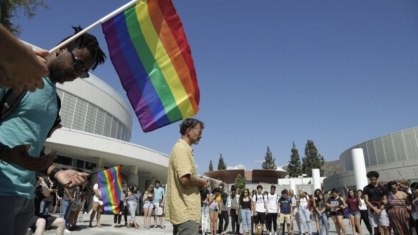 Rob Muthiah, a professor of practical theology, offers a prayer during a rally by the LGBTQ Christian community at Azusa Pacific University.