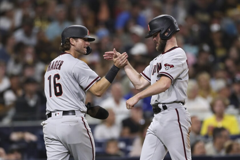 Arizona Diamondbacks' Jake Hager, left, celebrates with Matt Peacock after they scored on a single by Nick Ahmed against the San Diego Padres during the fourth inning of a baseball game Friday, Aug. 6, 2021, in San Diego. (AP Photo/Derrick Tuskan)