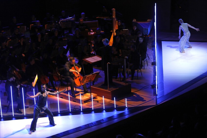 Flanked by Tero Saarinen Company dancers on the Walt Disney Concert Hall stage, cellist Timothy Loo plays his solo part with Susanna Mälkki nearby on the conductor's podium.