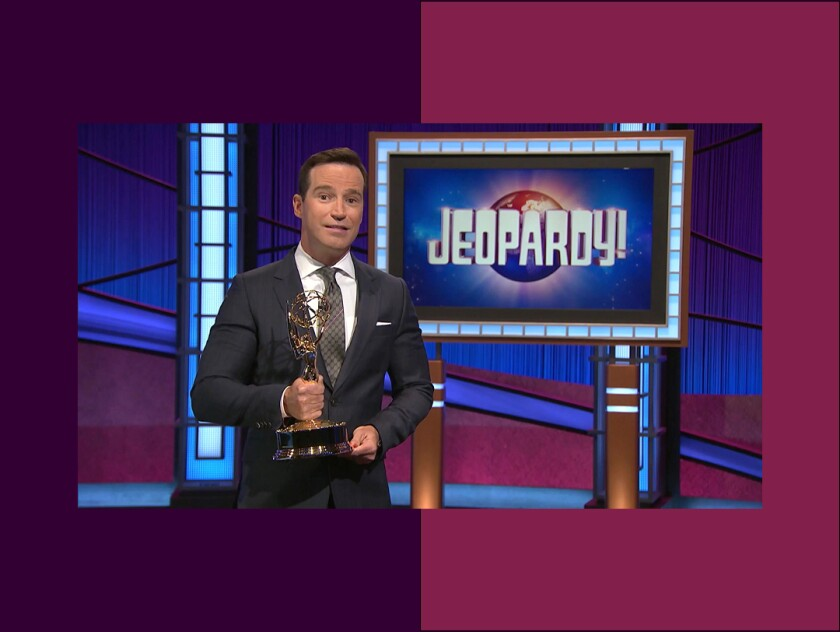 """Mike Richards holds an Emmy statue on the set of """"Jeopardy!"""""""