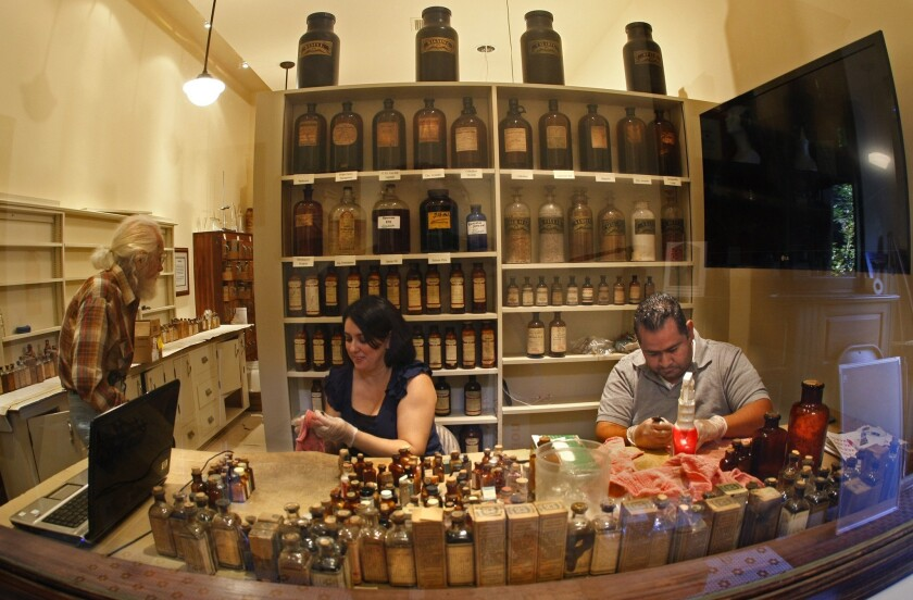 Volunteers Daniele Pineda and her husband Carlo clean decades of dust from early 20th century medicine bottles. Here in the pharmacy of the Colonial Drug museum at Heritage Square in Highland Park, visitors will be able to watch a video about the business once owned and operated by the Simmons family.