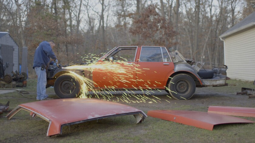 """Tommy Walkowiak working on one of his cars in the documentary """"The Last Race."""""""