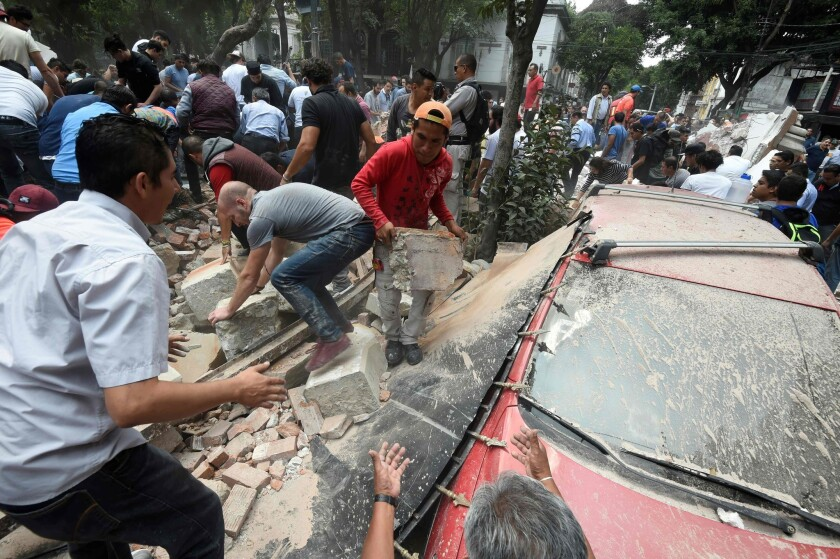 People in Mexico City remove debris after a building collapsed in a powerful earthquake on Tuesday.