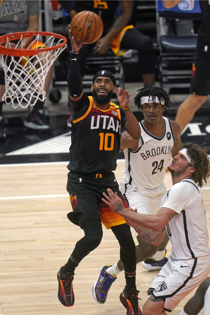 Utah Jazz guard Mike Conley (10) shoots as Brooklyn Nets' Alize Johnson (24) and Tyler Johnson, right, defend in the first half during an NBA basketball game Wednesday, March 24, 2021, in Salt Lake City. (AP Photo/Rick Bowmer)