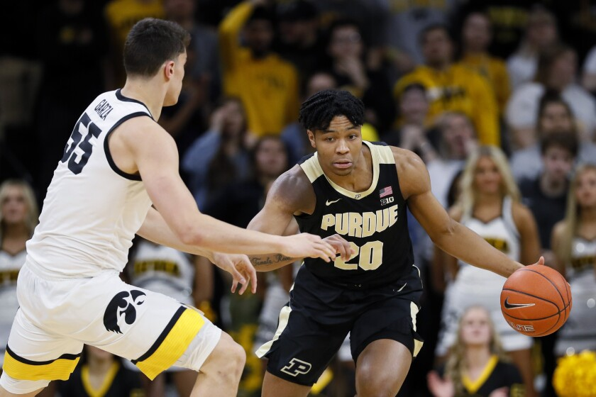 Purdue guard Nojel Eastern drives past Iowa center Luka Garza, left, during the first half of an NCAA college basketball game Tuesday, March 3, 2020, in Iowa City, Iowa. (AP Photo/Charlie Neibergall)