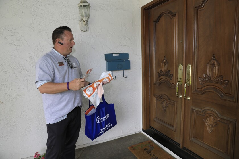 Realtor Robert Weichelt goes door to door in the Bay Ho neighborhood Saturday to explain why it is important to safely dispose of unneeded prescription pills as part of the Keep Kids Safe program.