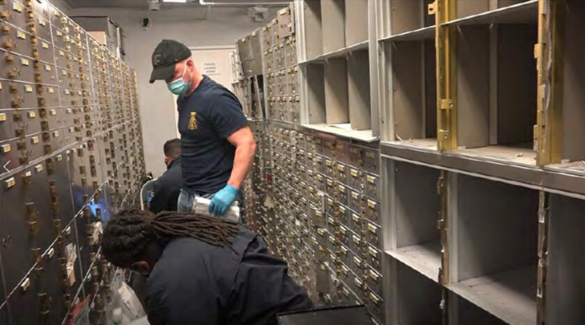 A man in an FBI T-shirt, mask and gloves, stands and two others kneel inside a vault.