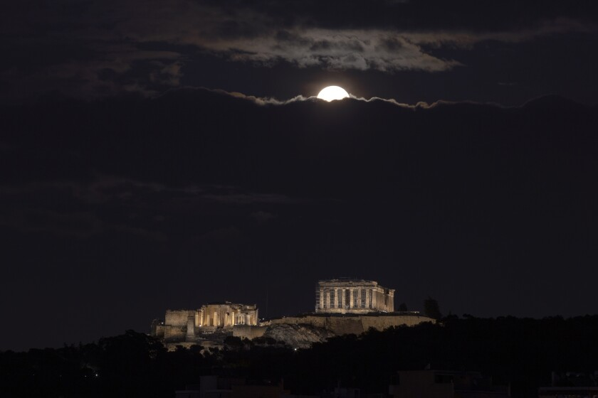 The full moon rises on the Athenian sky above the ancient Acropolis hill during cloudy night , on Monday, Nov. 30, 2020. (AP Photo/Petros Giannakouris)