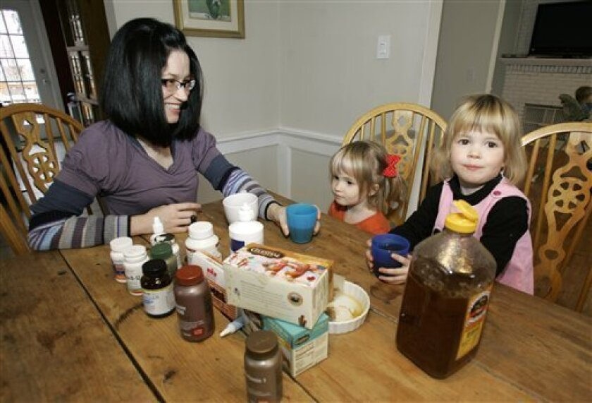 Kristen Kemp, left, has a cup of herbal tea with her three-year-old twin daughters, Annabelle, right, and Estelle at their home in Montclair, N.J., Thursday, Dec. 18, 2008.  Kemp uses home remedies and herbal medicine for her kids' sore throats and colds instead of prescription medications to cut c
