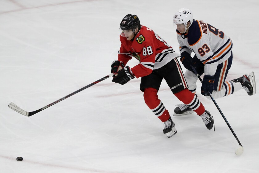 """FILE - In this March 5, 2020, file photo, Chicago Blackhawks right wing Patrick Kane, left, and Edmonton Oilers center Ryan Nugent-Hopkins chase the puck during the third period of an NHL hockey game in Chicago. Assuming everything goes according to plan and the final details are ironed out between the league and the players' union, the Blackhawks will play the Oilers in a best-of-five qualifier series for the playoff bracket. """"It's been a weird three months,"""" Kane said during a video conference call with reporters. (AP Photo/Nam Y. Huh, File)"""