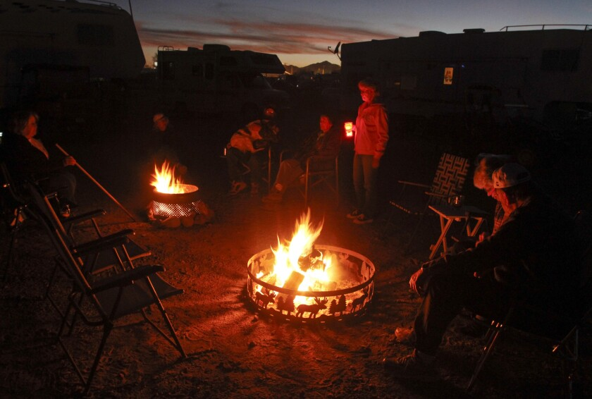 People gather around a fire at an motor home park in Quartzsite, Ariz.
