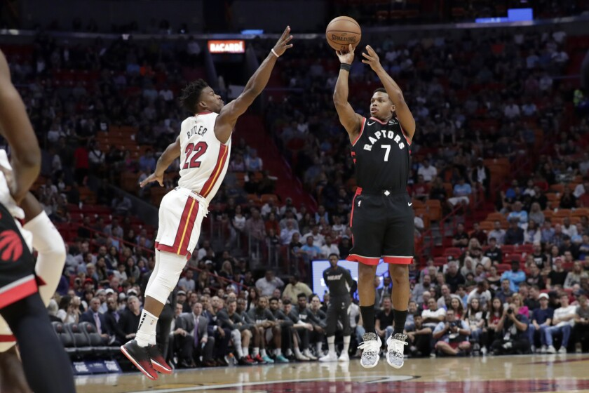 Toronto Raptors guard Kyle Lowry (7) attempts a 3-pointer as Miami Heat forward Jimmy Butler (22) defends during the first half of an NBA basketball game, Thursday, Jan. 2, 2020, in Miami. (AP Photo/Lynne Sladky)