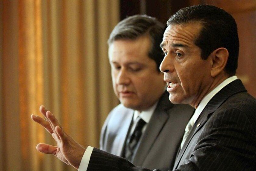 City Administrative Officer Miguel Santana, left, listens as Mayor Antonio Villaraigosa responds to a question about the AEG sale during a news conference at Los Angeles City Hall.