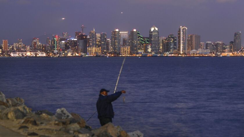 With the downtown San Diego skyline in the background, a fisherman inspects a fish he caught off Harbor Island.