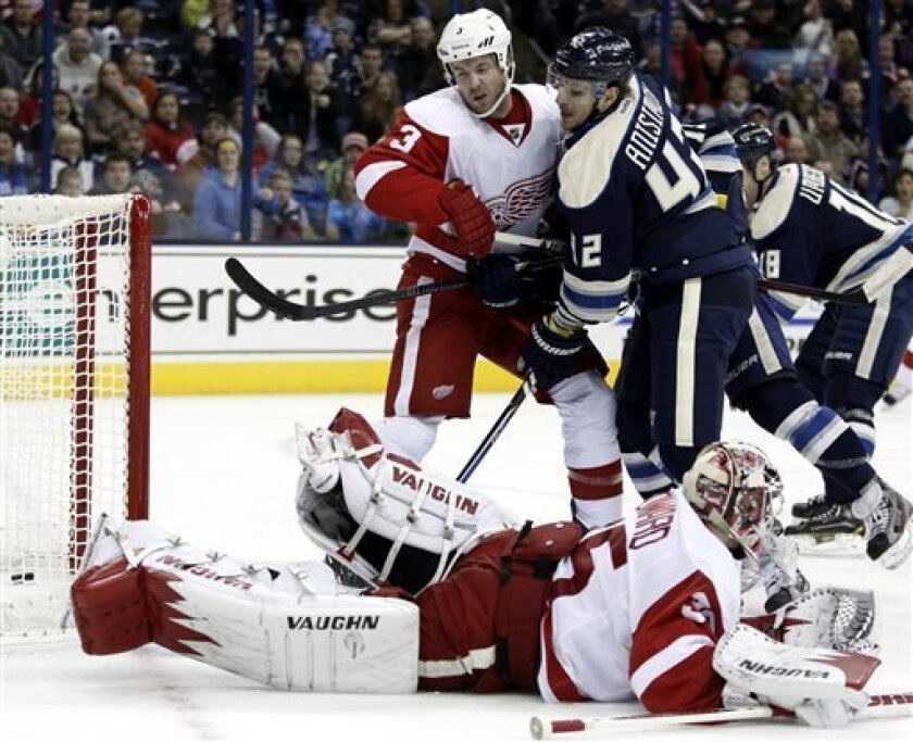 Columbus Blue Jackets' Artem Anisimov (42) scores against Detroit Red Wings' Kent Huskins (3) and goalie Jimmy Howard (35) in the second period of an NHL hockey game in Columbus, Ohio, Saturday, Feb. 2, 2013. (AP Photo/Paul Vernon)