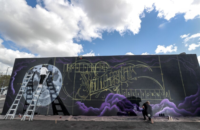 """Artists Carla Ricci, left, and Aleck Christian, founder of Beautiful San Diego, work on a mural which will say """"South Park"""" on back of The Bottle House liquor store in South Park Thursday."""