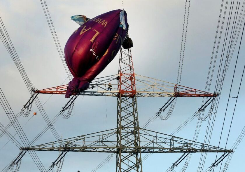 A hot air balloon sits on top of a high-voltage power line in Bottrop, Monday, Oct. 1, 2018 after it collided the evening before.