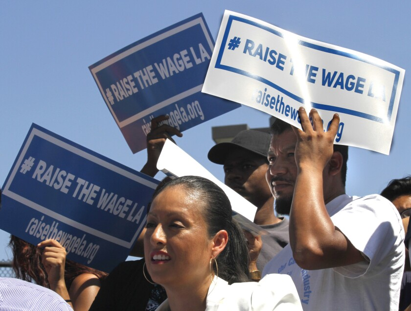 Supporters listen to L.A. Mayor Eric Garcetti announce his plan to raise the minimum wage in the city to more than $13 an hour.