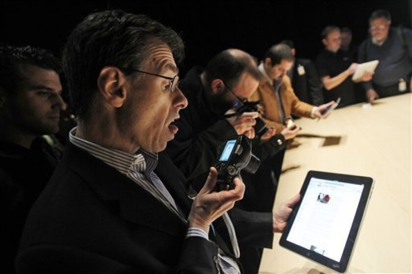 FILE - In this Jan. 27, 2010 file photo, the Apple iPad is examined after its unveiling at the Moscone Center in San Francisco. (AP Photo/Marcio Jose Sanchez, file)