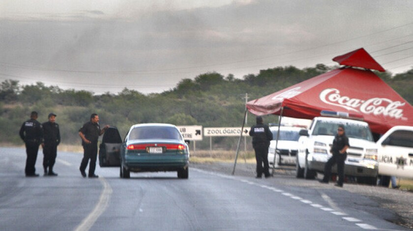 Mexican police operate a checkpoint on the highway that follows the Rio Grande River outside Reynosa.
