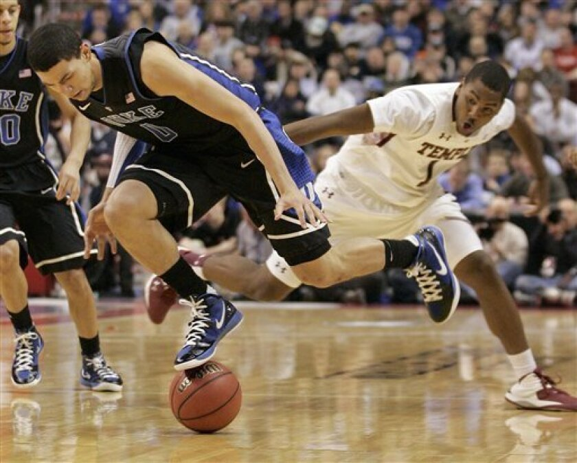 Duke's Austin Rivers, left, and Temple's Khalif Wyatt chase a loose ball during the first half of an NCAA college basketball game, Wednesday, Jan. 4, 2012, in Philadelphia. (AP Photo/Tom Mihalek)