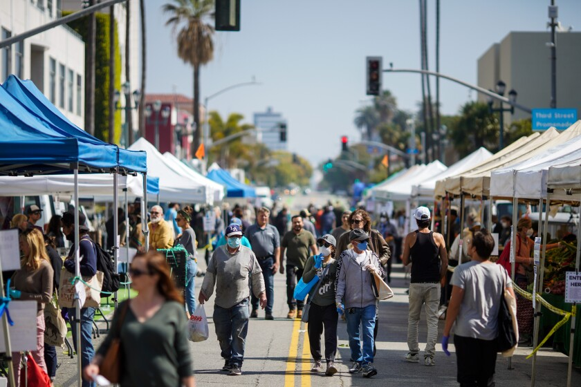 People wearing personal protective equipment shop at the Santa Monica Farmers Market on Wednesday in Santa Monica.