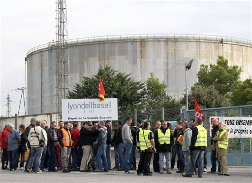 Oil refinery workers block their plant in Berre l'Etang, southern France, Wednesday Oct.13, 2010. Some oil workers pledged to keep up a protest at refineries, and one union warned of looming gasoline shortages. French commuters fought their way onto packed subways and buses on Wednesday as an open-