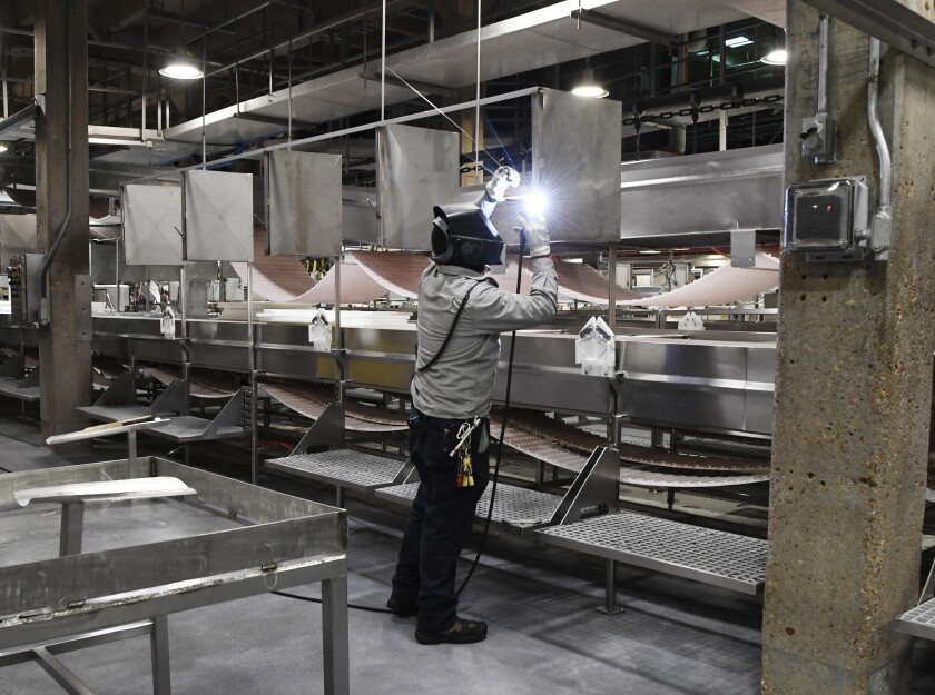 A welder in protective gear working inside a meat plant.