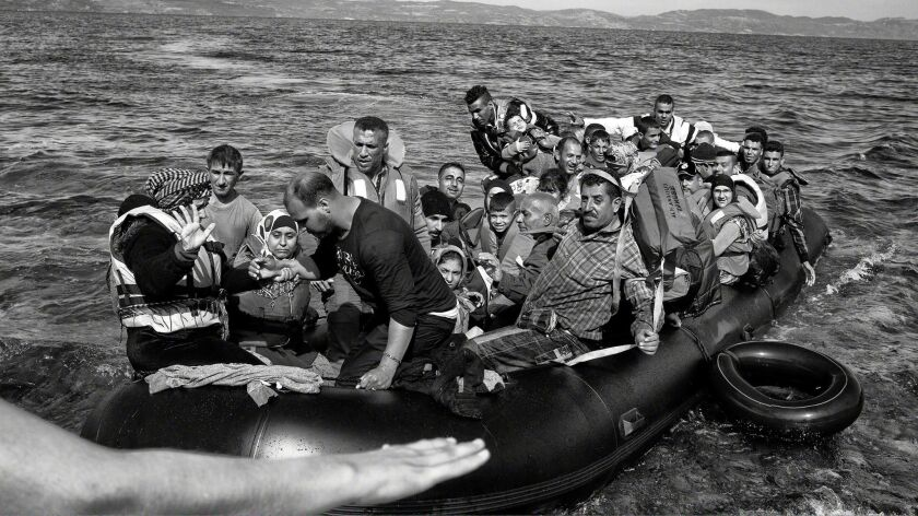 A rubber boat packed with refugees and migrants lands on the shoreline of Lesbos, Greece, after crossing the Aegean Sea from Turkey in 2015.