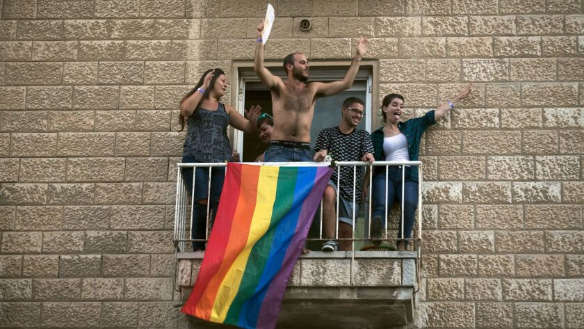 Israelis celebrate on their balcony during the parade in Jerusalem.