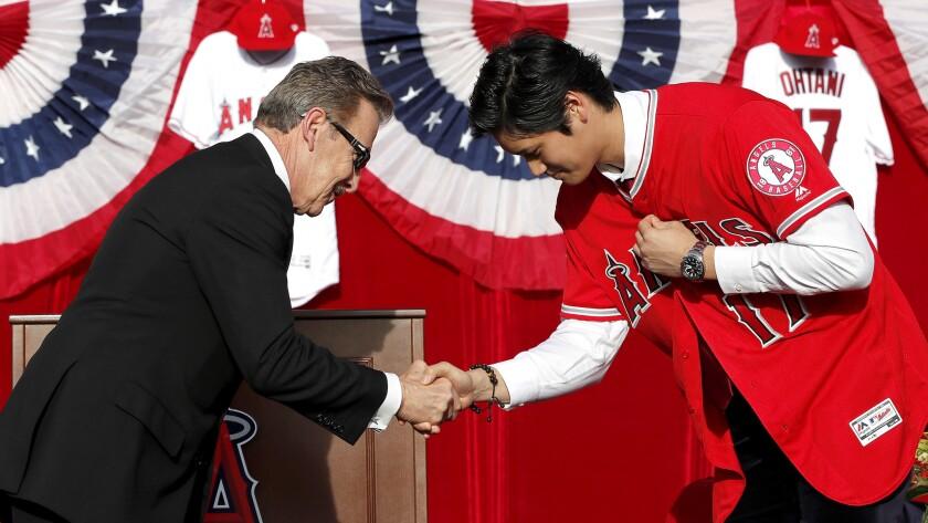 "ANAHEIM, CALIF. -- SATURDAY, DECEMBER 9, 2017 Arturo ""Arte"" Moreno, left, bows and congratulates J"
