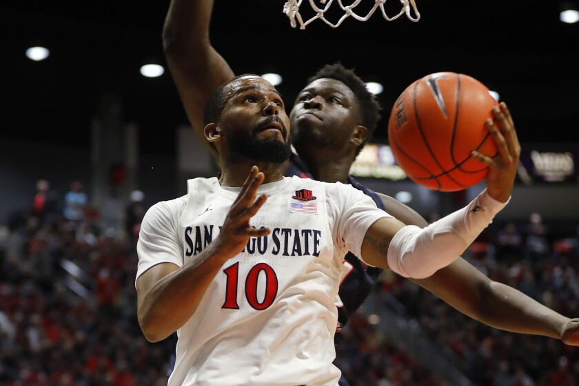 San Diego State's KJ Feagin scores in front of against Fresno State's Assane Diouf on Jan. 1, 2020.