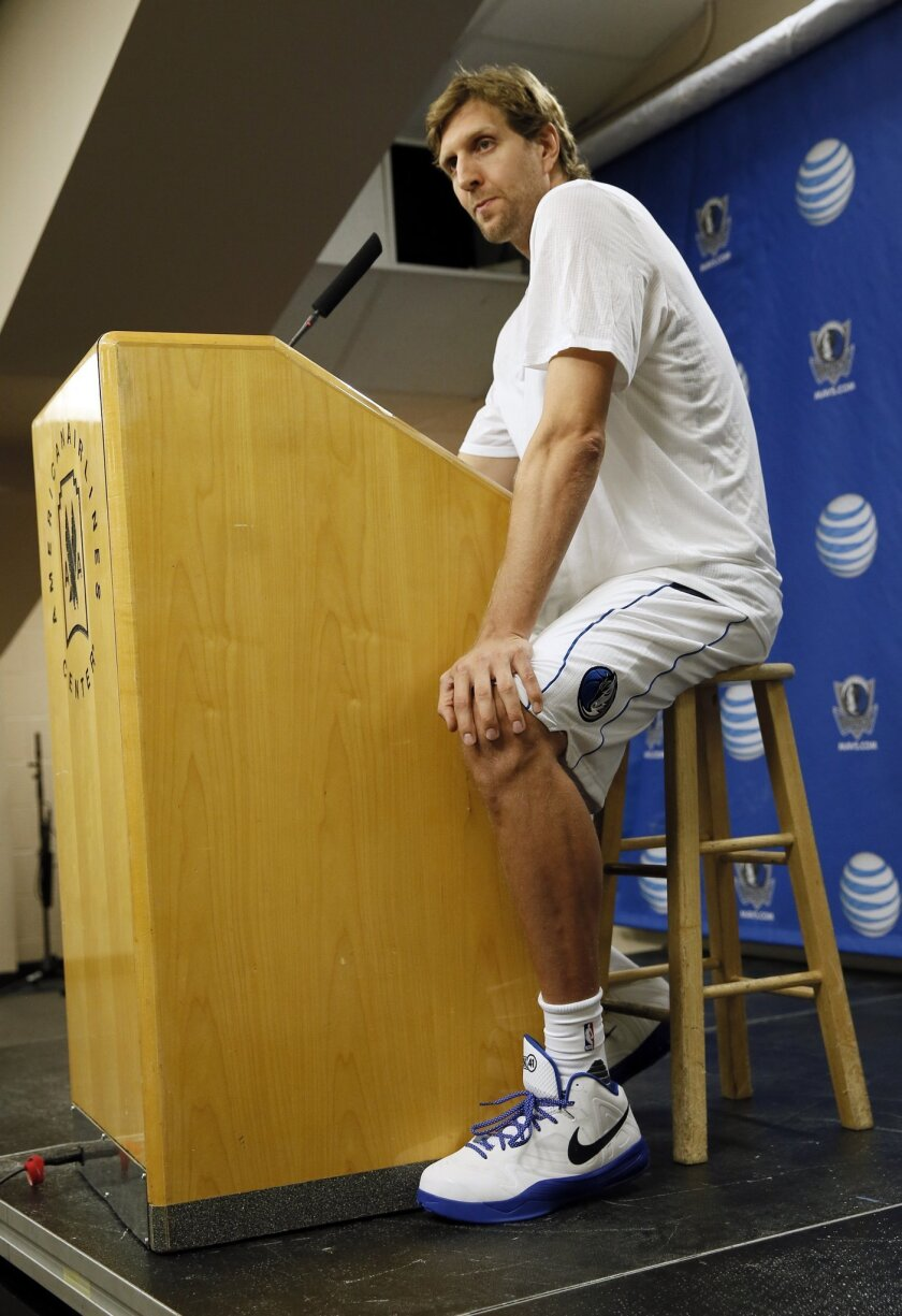 Dallas Mavericks' Dirk Nowitzki, of Germany, sits at the podium responding to questions during a news conference at an NBA basketball media day Monday, Sept. 28, 2015, in Dallas. (AP Photo/Tony Gutierrez)