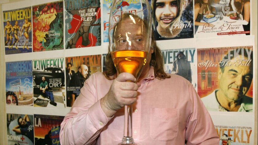 Jonathan Gold worked the city as a sort of culinary troubadour. Here, he holds up a giant glass of Champagne after winning the Pulitzer Prize in 2007 at L.A. Weekly, as if trying to protect his identity.