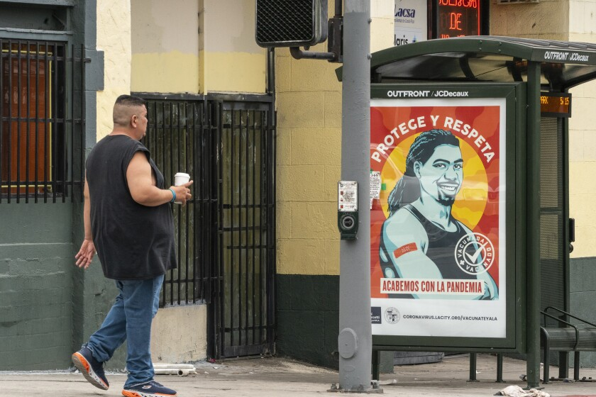 """A pedestrian walks past a banner promoting vaccinations at the Pico-Union district in Los Angeles, Monday, July 26, 2021. The City of Los Angeles advertisement reads in Spanish: """"Protect and Respect, Let's End the Pandemic."""" Pico-Union is the fourth most dense neighborhood in Los Angeles, home to a large immigrant community. The state of California said it would require proof of vaccination or weekly testing for all state workers and millions of public- and private-sector health care employees starting in August. (AP Photo/Damian Dovarganes)"""