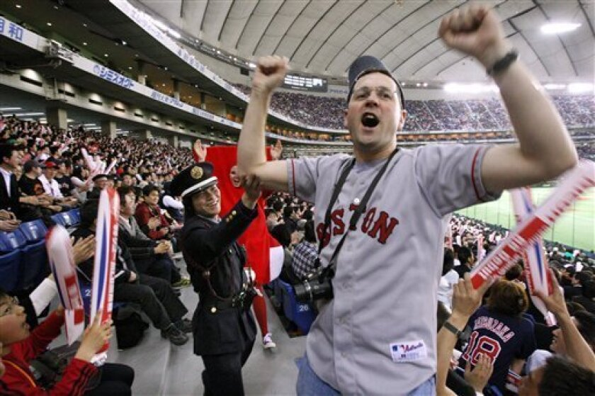 A Japanese security guard asks Rob Crawford, vice president of the Red Sox Nation, to sit down in his seat as he tries to get the Japanese crowd excited in the ninth inning of the Major League Baseball regular season opener between the Red Sox and the Oakland Athletics at Tokyo Dome in Tokyo Tuesday, March 25, 2008. (AP Photo/David Guttenfelder)