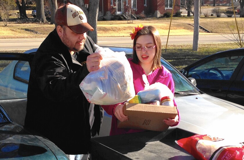 Joe Heflin and a volunteer load groceries into his car at the Samaritan Center food pantry in Jefferson City, Mo. Heflin, 33, also receives food stamps but could lose them if he doesn't meet newly enforced work requirements.