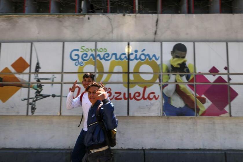 Dos jóvenes fueron registrados frente a un mural del Ministerio del Deporte en el que se publicitaba la denominada generación del deporte venezolano, en Caracas (Venezuela). EFE