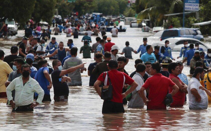 Múltiples personas vadean un camino inundado tras el paso del huracán Eta,