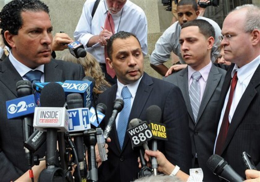 Police officer Ken Moreno, middle with co-defendant Franklin Mata, right, speak to the media outside Manhattan criminal court, Thursday, May 26, 2011, in New York. Moreno and Mata have been acquitted of rape, but convicted of official misconduct. The officers were called to help a drunken woman get out of a taxi in December 2008. The woman testified that she passed out and awoke to being raped in her apartment. Moreno told jurors he lay alongside her in her bed for a while, but they didn't have sex. Mata was accused of acting as a lookout. He said he was napping in the living room while the others were in the bedroom. (AP Photo/ Louis Lanzano)