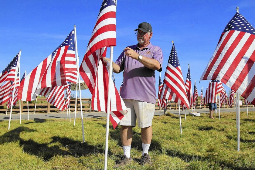 Rick Anderson, a member of the Exchange Club of Newport Harbor board of directors, labels one of 1,776 American flags during the fifth annual Field of Honor at Castaways Park in Newport Beach on Friday.