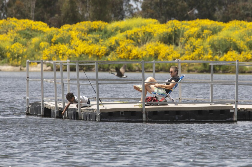"""Erin Rose and her four-year-old son Jaxon social-distanced as they fished from a pier at the reopened Chollas Lake Park in Oak Park on Tuesday. """"The fact that we can be outside and not cooped up now is life changing,"""" Rose said."""