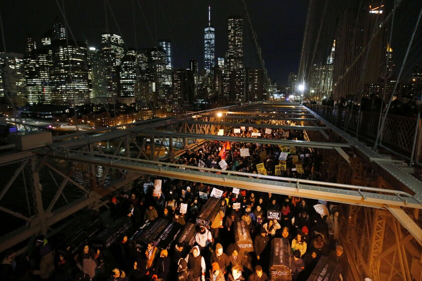 Protesters carry a collection of mock coffins bearing the names of victims of fatal police encounters as they cross the eastbound traffic lanes of the Brooklyn Bridge.