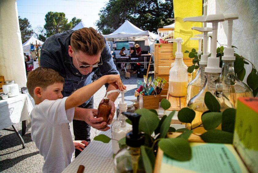 Jasper Watts helps his 5-year-old son, James, pump shampoo into a glass container from Sustain L.A.'s refill station at the Altadena Farmers Market.